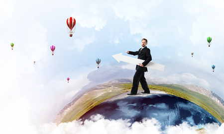 Conceptual image of young successful business man in suit pointing aside by means of big white banner in form of arrow while standing on Earth globe. Elements of this image are furnished by NASA.