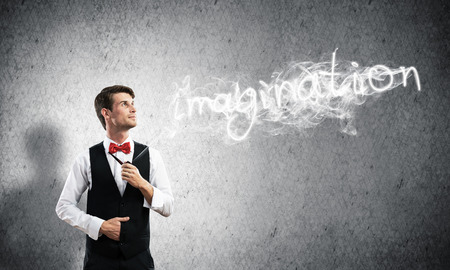 Horizontal shot of confident and young businessman in smart-casual wear smoking pipe while standing against gray dark wall and imagination word made from smoke on background. Imagens - 112743032