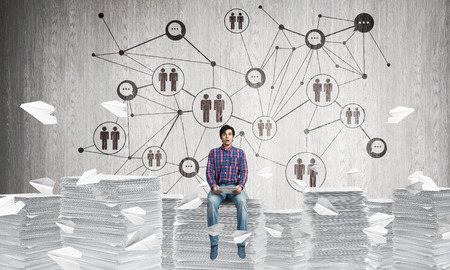 Young man in casual wear sitting on pile of documents among flying paper planes with social network structure on background. Mixed media.