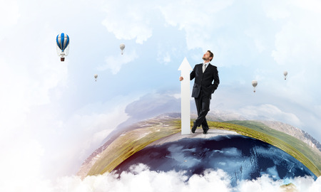 Confident and young businessman in suit holding big white arrow in hand which pointing aside while standing on Earth globe and sky view on background. Elements of this image are furnished by NASA Stock Photo
