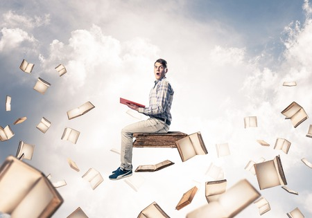 Young shocked man floating in blue sky with red book in hands Stock fotó
