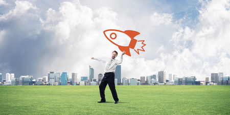 Confident and young businessman in suit starting launching a big rocket from his hand while standing on green meadow and city view on background. Stock Photo