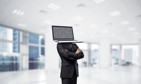 Cropped image of businessman in suit with laptop instead of head keeping arms crossed while standing inside office building. Stockfoto
