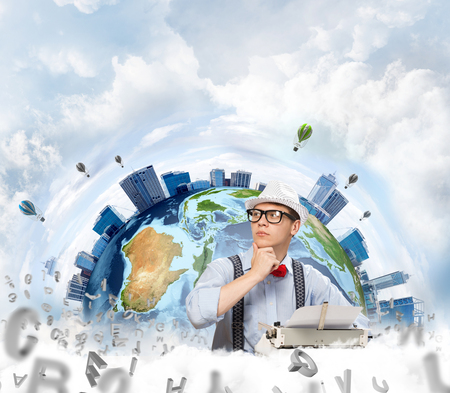 Thoughtful  writer in hat and eyeglasses looking away and touching chin while using typing machine with flying letters and Earth globe among cloudy skyscape on background. Elements of this image furnished by