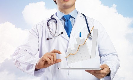 Young doctor in sterile medical suit presenting tablet with graphical chart in hands while standing against cloudy skyscape view on background.