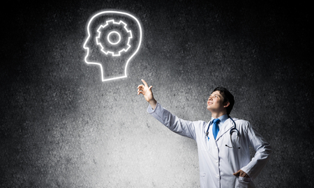 Confident doctor in white uniform interracting with glowing gear brain symbol while standing against gray dark wall on background. Stock Photo