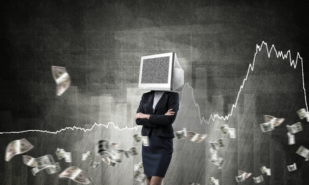 Business woman in suit with monitor instead of head keeping arms crossed while standing against flying dollars and analytical charts drawn on wall on background. 3D rendering.