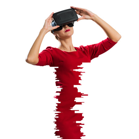 Beautiful and young woman in red dress using virtual reality headset while standing against white background. Up to date technologies Stock Photo