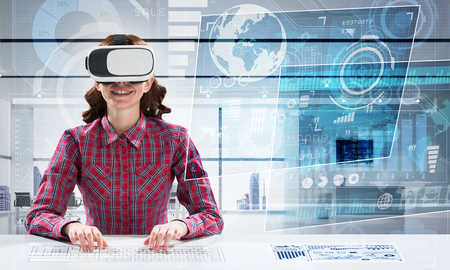 Modern technologies for education by means of young female student in checkered shirt using virtual reality goggles and interracting with digital media interface.