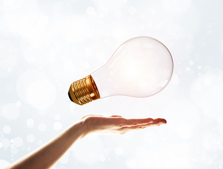 Close of male palm holding glass light bulb on bokeh background Stock Photo