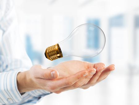 Nahaufnahme von Geschäftsmann in Händen halten Glas Glühbirne. Gemischte Medien Standard-Bild