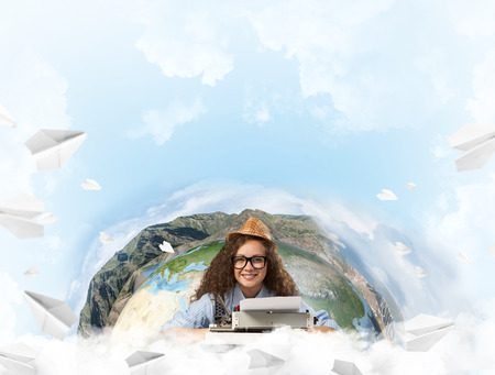 Hard-working female writer using typing machine while sitting at the table with flying paper planes and Earth globe among cloudy skyscape on background. Elements of this image furnished by NASA