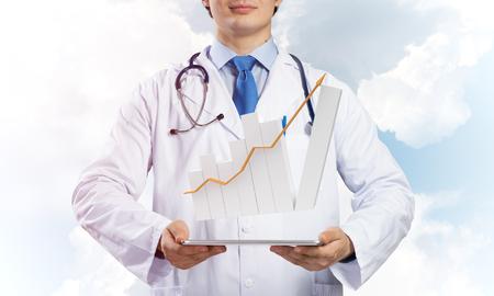 Joven médico en traje médico estéril presenta tableta con gráfico en las manos mientras está de pie contra la vista de cielo nublado en el fondo.