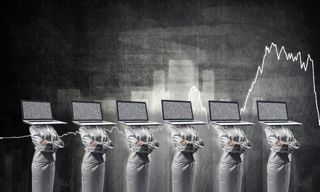 Business women in suits with laptops instead of their heads keeping arms crossed while standing against analytical charts drawn on wall on background. Stock Photo