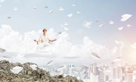 Young man keeping eyes closed and looking concentrated while meditating on cloud among flying paper planes with city view on background.