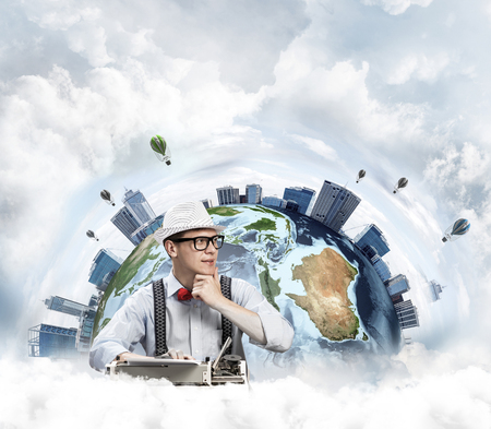 Thoughtful man writer in hat and eyeglasses looking away and touching chin while using typing machine with Earth globe and cloudy skyscape on background.