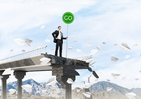 Confident businessman in suit holding green go sign while standing among flying paper planes on broken bridge with skyscape and nature view on background. 3D rendering.