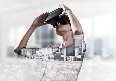 Double exposure of young and beautiful woman in red dress using virtual reality headset while standing indoors of office building with digital network structure. Stock Photo - 113760303