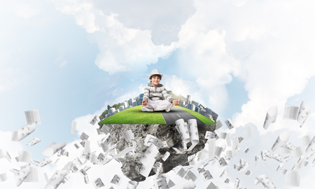 Young little boy keeping eyes closed and looking concentrated while meditating on flying island among flying papers with cloudy skyscape on background. 3D rendering. Imagens