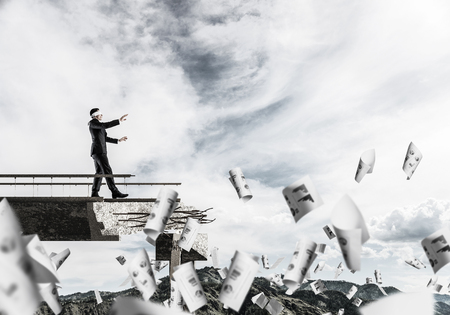 Businessman walking blindfolded among flying papers on concrete bridge with huge gap as symbol of hidden threats and risks. Skyscape and nature view on background. 3D rendering.