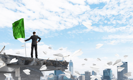 Rear view of confident businessman in suit holding flag in hand while standing among flying paper planes on broken bridge with cityscape on background. 3D rendering.