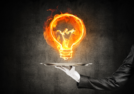 Cropped image of waitresss hand in white glove presenting flaming lightbulb on metal tray with dark wall on background. Stock Photo