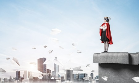 Young girl in superhero costume standing on building roof. Mixed media