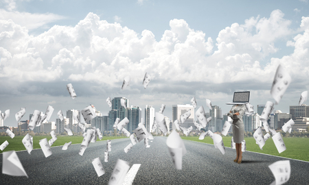 Business woman in suit with laptop instead of head keeping arms crossed while standing on the road among flying papers with beautiful landscape on background.