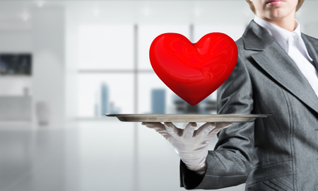 Cropped image of waitresss hand in white glove presenting big red heart on metal tray with office view on background.
