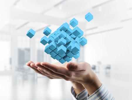 Près de la main d'homme d'affaires tenant la figure de cube comme symbole de l'innovation. Rendu 3D