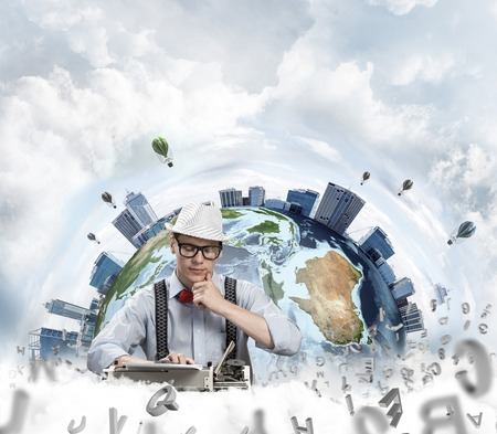 Thoughtful man writer looking away and touching chin while working with typing machine at the table, flying letters and Earth globe among cloudy skyscape on background. Stock Photo