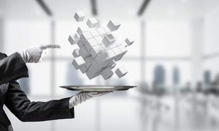 Cropped image of waiters hand in white glove presenting multiple cubes on metal tray with office view on background. 3D rendering.