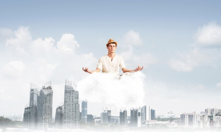 Man in white clothing keeping eyes closed and looking concentrated while meditating on cloud above wooden floor with cityscape view on background. Stock Photo