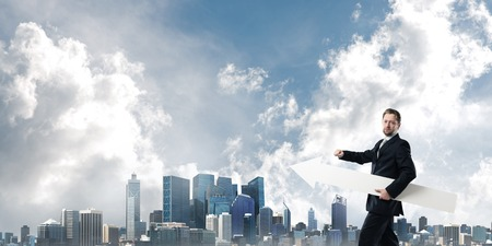 Cropped image of successful young businessman holding big white arrow and pointing away while standing against cityscape view on background