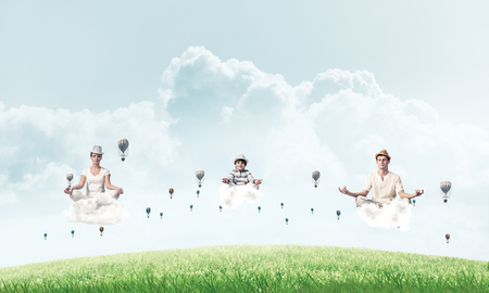 Young family keeping eyes closed and looking concentrated while meditating on clouds among flying aerostats with bright and beautiful landscape on background. Standard-Bild