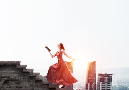 Young attractive woman in red dress with book in hand walking up staircase. Mixed media 版權商用圖片
