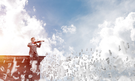 Young man wearing suit and glasses sitting on top and playing violin