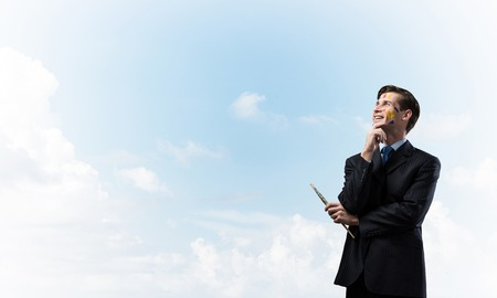 Portrait of confident young man holding paintbrush in his hand and looking away while standing against blue cloudy skyscape on background. Stock Photo