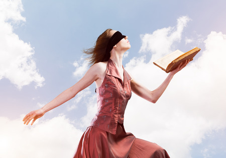 Young woman in red long dress and blindfold with book in hand Stock fotó