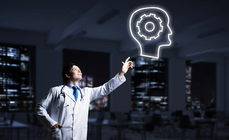 Conceptual image of confident doctor in white uniform interracting with glowing gear brain symbol while standing against night cityscape view on background.