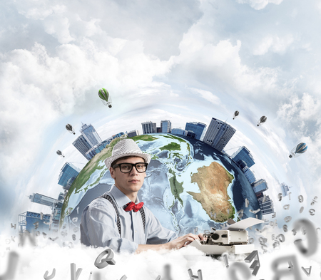 Young man writer in hat and eyeglasses using typing machine while sitting at the table with flying letters and Earth globe among cloudy skyscape on background.