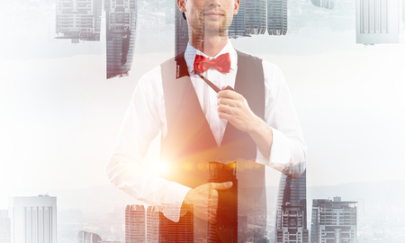 Double exposure of confident and young businessman in smart-casual wear smoking pipe and two modern urban worlds on background. Concept of young and successful entrepreneur.