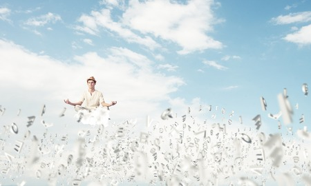 Man in white clothing keeping eyes closed and looking concentrated while meditating among flying letters in the air with cloudy skyscape on background. 版權商用圖片