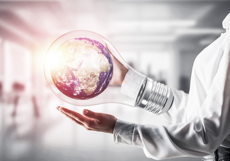 Cropped image of businessman in shirt holding lightbulb with Earth globe inside in his hands. Sunlight on office view background. Elements of this image are furnished by NASA