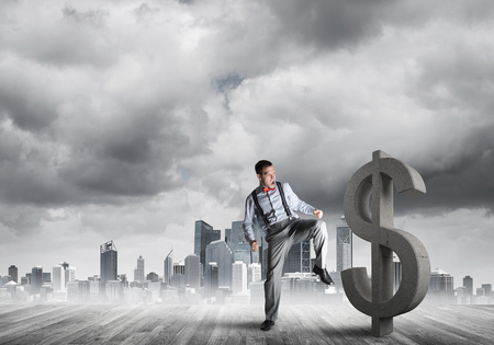 Young furious businessman going to crash with kick stone dollar symbol Stock Photo