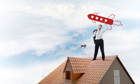 Successful and young businessman standing on the top of brick roof and throwing huge red rocket in the air with cloudy skyscape view on background. Stock Photo