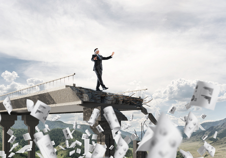 Businessman walking blindfolded among flying documents on concrete bridge with huge gap as symbol of hidden threats and risks. Skyscape and nature view on background. 3D rendering. Stockfoto