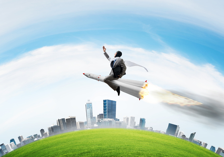 Conceptual image of young businessman in suit flying on rocket with cityscape and blue sky on background.
