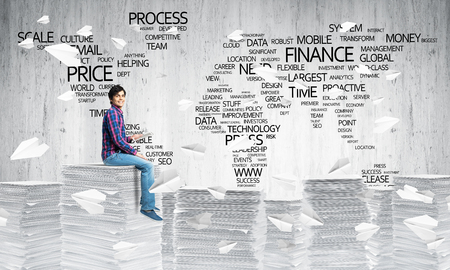 Young man in casual wear sitting among flying paper planes with business-related terms in form of world map on background. Mixed media.