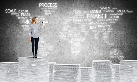 Woman in casual wear standing on pile of documents with speaker in hand with business-related terms in form of world map on background. Mixed media.
